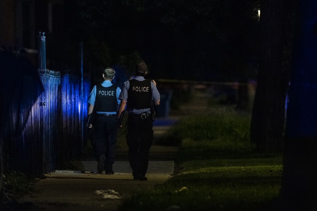 Police investigate the scene where a 12-year-old boy was shot August 14, 2020, in Woodlawn.