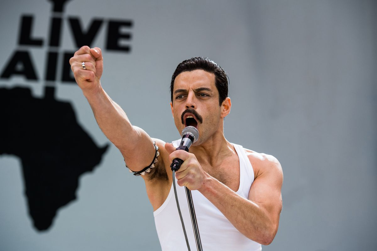 Rami Malek as Freddy Mercury wearing a white tank top on stage with his fist up