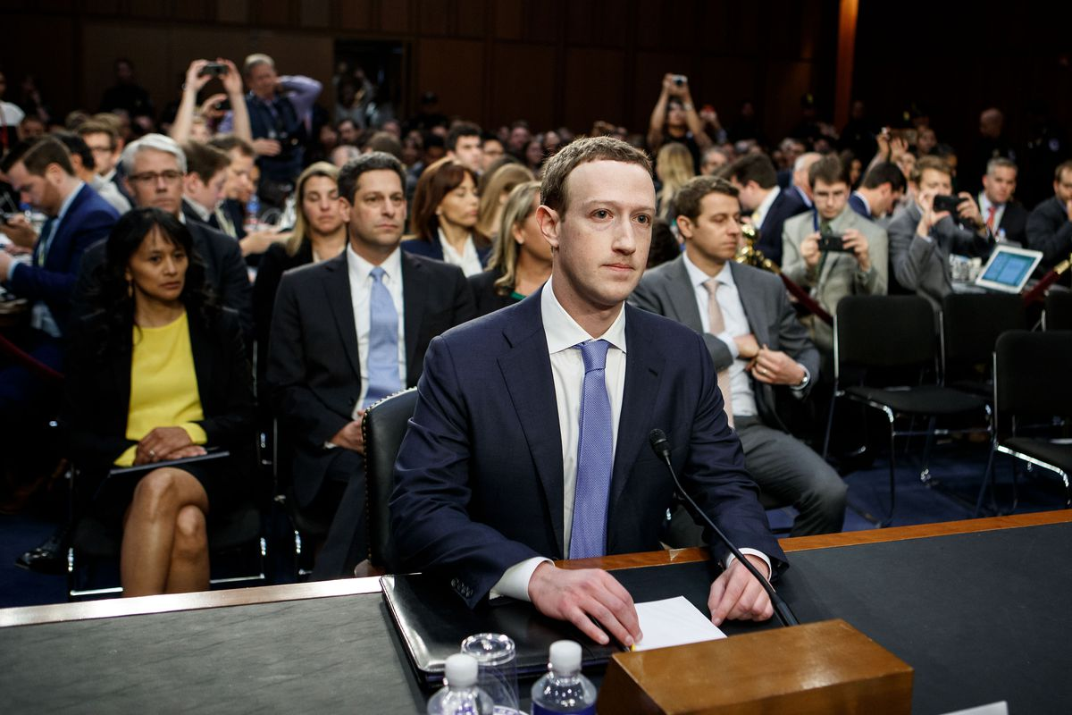 Facebook CEO Mark Zuckerberg sitting at a desk and wearing a suit and tie for his testimony before Congress in 2018. The room behind him is packed with seated people.