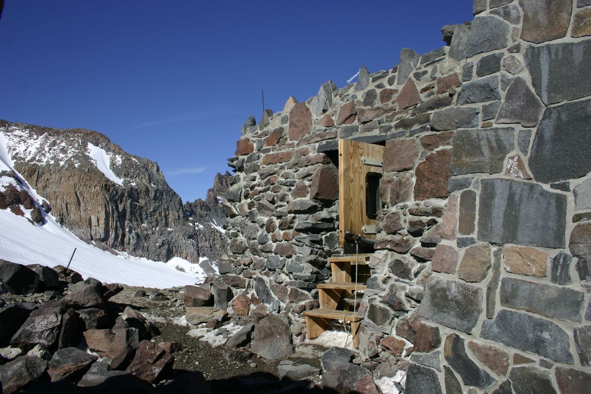 Camp Muir on Mount Rainier. The facade is stone and there is a wooden door and steps. In the background are mountains and snow.
