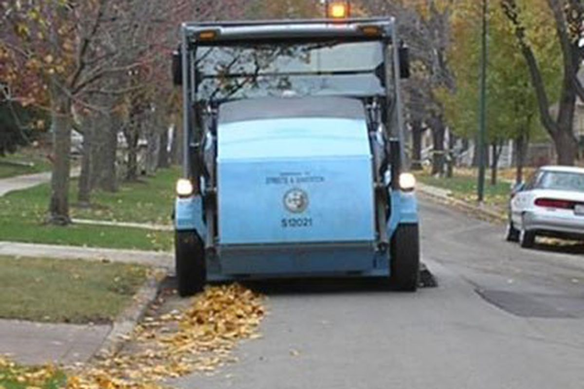 A street sweeper cleans a residential street.