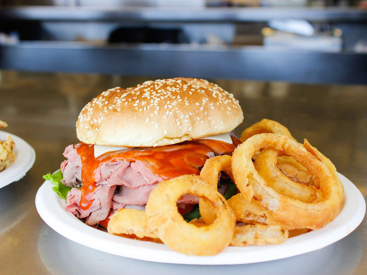 A roast beef sandwich with cheese, mayo, and barbecue sauce sits on a paper plate, accompanied by thick onion rings.
