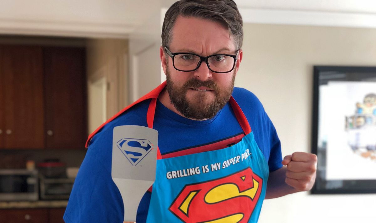 Greg Miller wearing his grilling outfit, a Superman apron, holding a Superman spatula