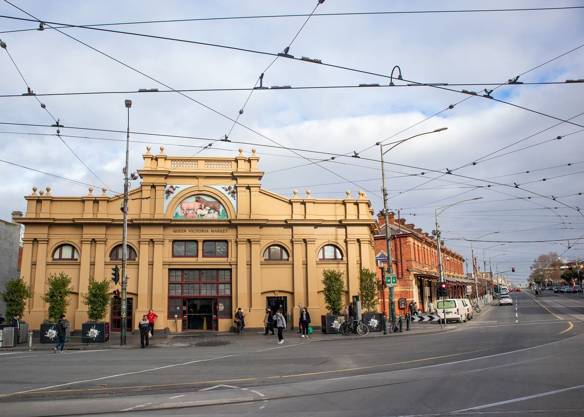 A criss cross of tram lines fill the sky in front of the historic Queen Victoria Market
