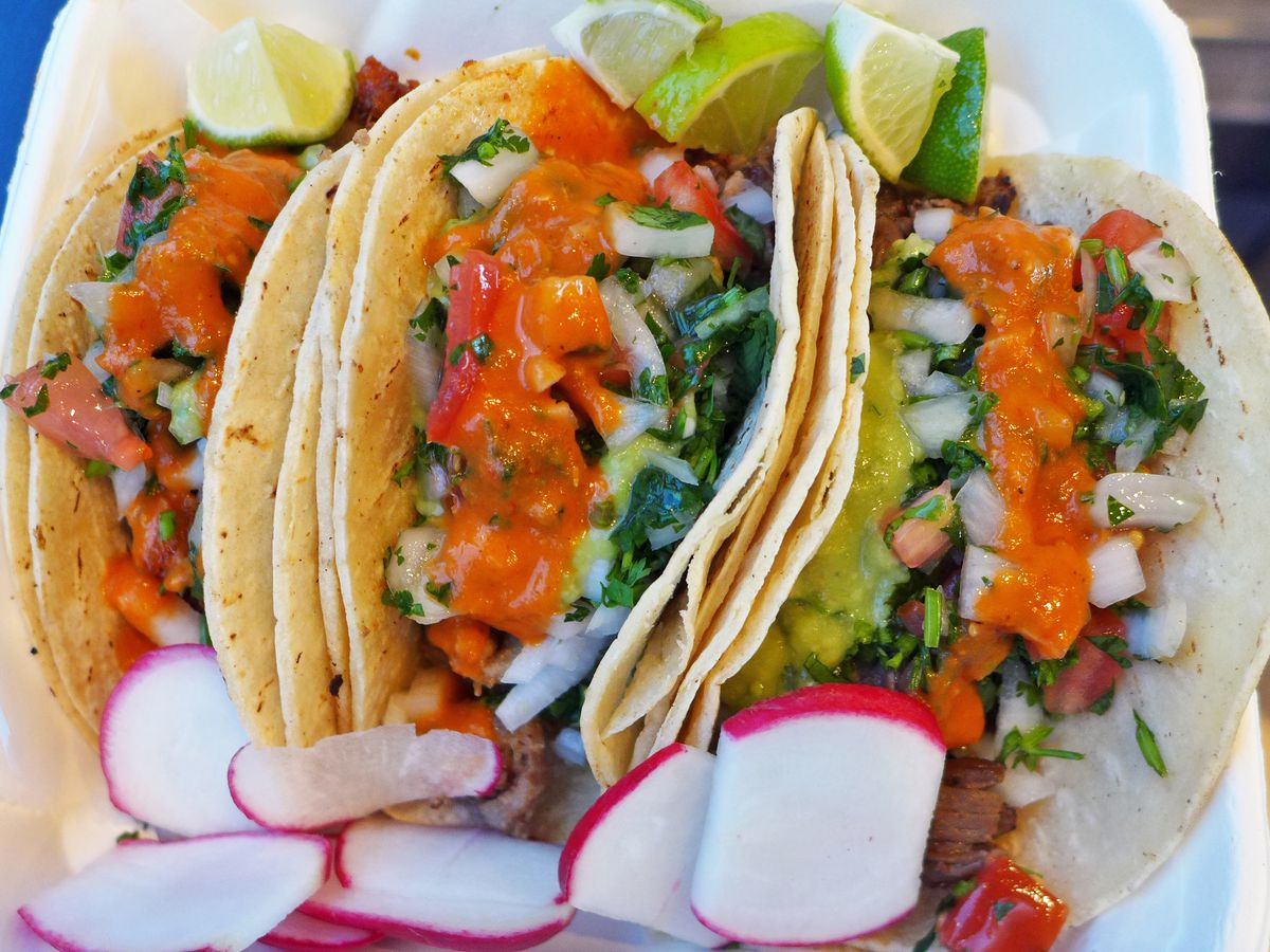 Three double tortilla tacos stuffed with meat and greenery and topped with red salsa