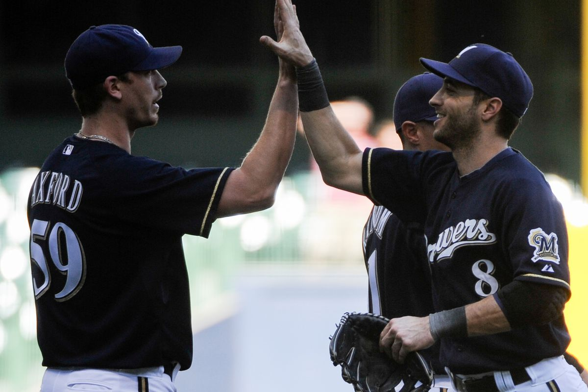 Aug 22, 2012; Milwaukee, WI, USA;   Milwaukee Brewers left fielder Ryan Braun (8) celebrates with pitcher John Axford (59) after the Brewers beat the Chicago Cubs 3-2 at Miller Park.  Mandatory Credit: Benny Sieu-US PRESSWIRE
