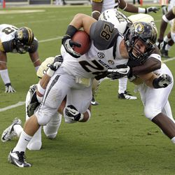 Missouri wide receiver T.J. Moe (28) is tackled after a short reception by Central Florida's Kevin Miller, right, and Jared Greenaway, during the first half of an NCAA college football game, Saturday, Sept. 29, 2012, in Orlando, Fla.