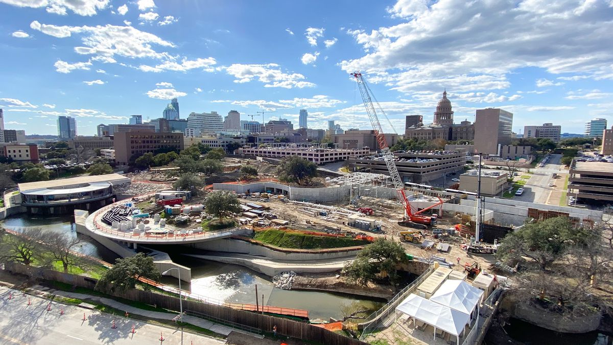 Aerial photo of a large construction site fronting a creek. There's a crane and smaller equipment on the ground. There's a bridge over the creek to a road in front.There are two flat, circular structures being built. There are medium and tall buildings across the background.