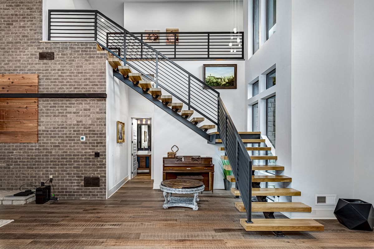 Open space with floating staircase leading upstairs.