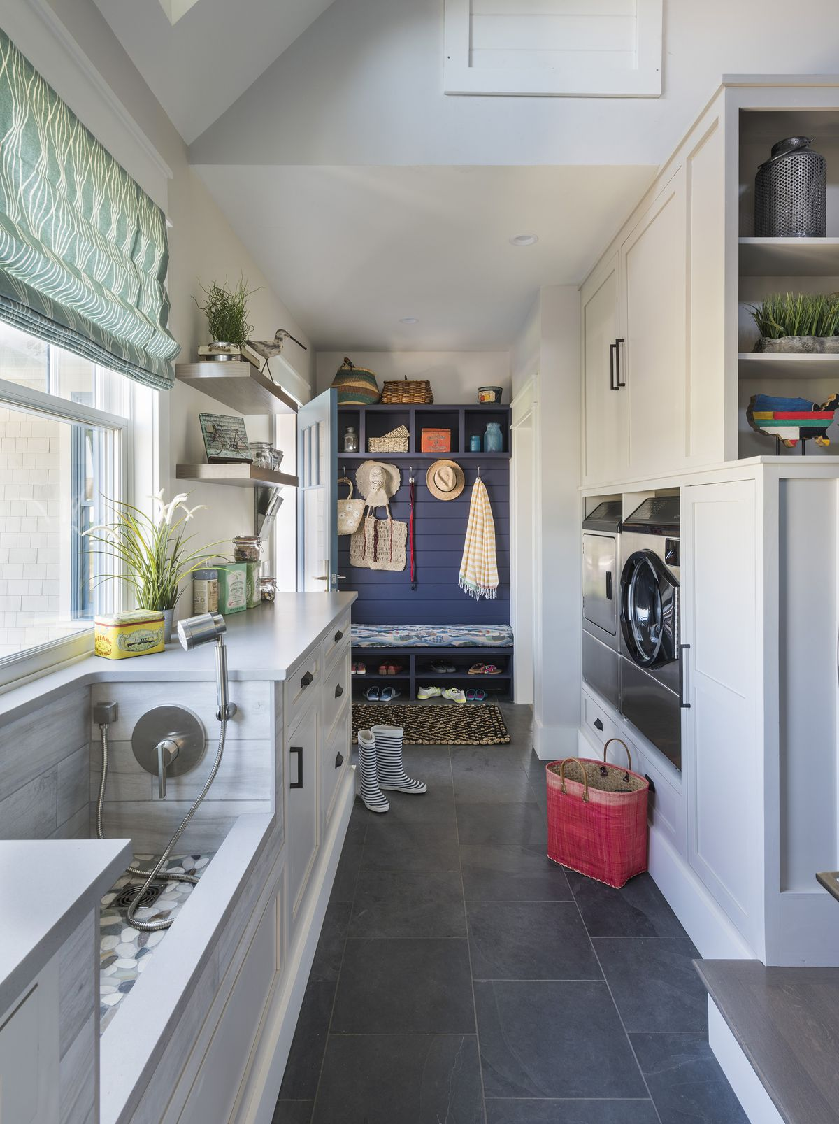 """<p>The side entry leads to a combination mudroom, laundry room, and pet-washing station.</p> <p><em>Paint: </em>Ceiling and trim in <a href=""""https://www.olympic.com/paint-colors/delicate-white-ol107"""" target=""""_blank"""">Delicate White</a>, <a href=""""https://www.olympic.com/paint-colors/swirling-smoke-ol196, walls in Shark https://www.olympic.com/paint-colors/shark-ol222"""" target=""""_blank"""">Cabinets in Swirling Smoke</a>, cubbies in <a href=""""https://www.olympic.com/paint-colors/black-flame-ol7546"""" target"""
