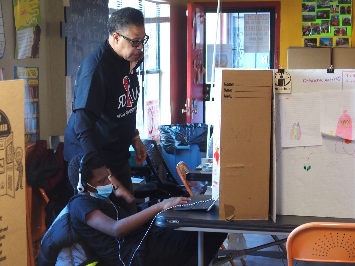 Red Door Urban Missions founder Eric Hawkins helps a student with his online class who is sitting at a table with a cardboard divider.