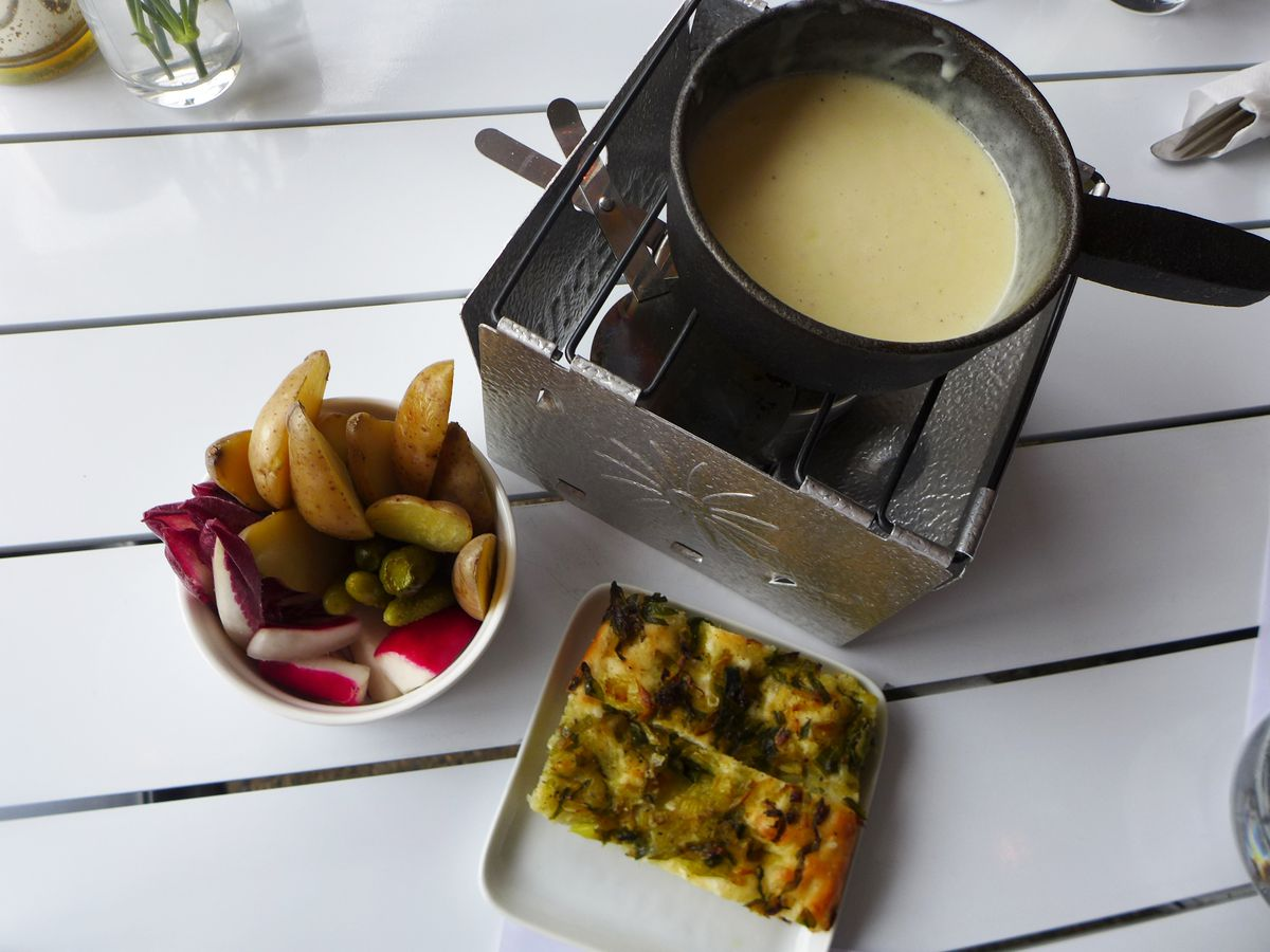 On a white outdoor table a reservoir of cheese sauce, little plate of focaccia, and bowl of crudite for dipping.