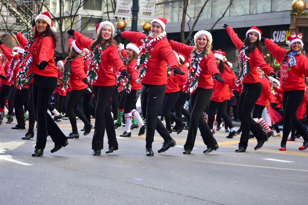People in a parade in Chicago. The people are all dressed in outfits with black pants and red tops.