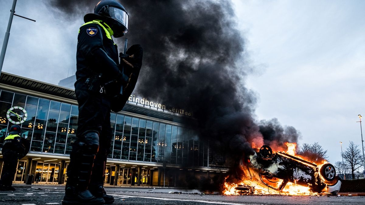 A person dressed in a helmet and riot gear stands near an upside-down burning vehicle.