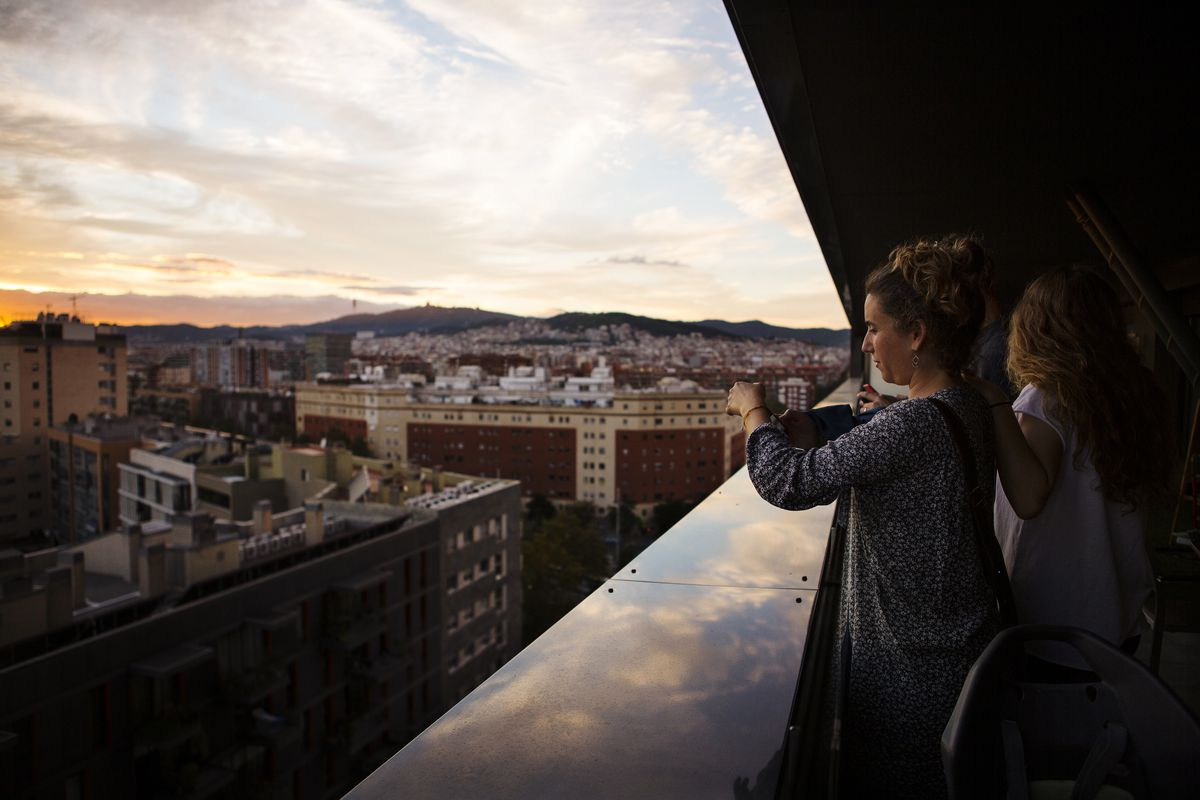 Poblenou resident Silvia Casorrán takes a picture at sunset, from an apartment perched high above the superblock.