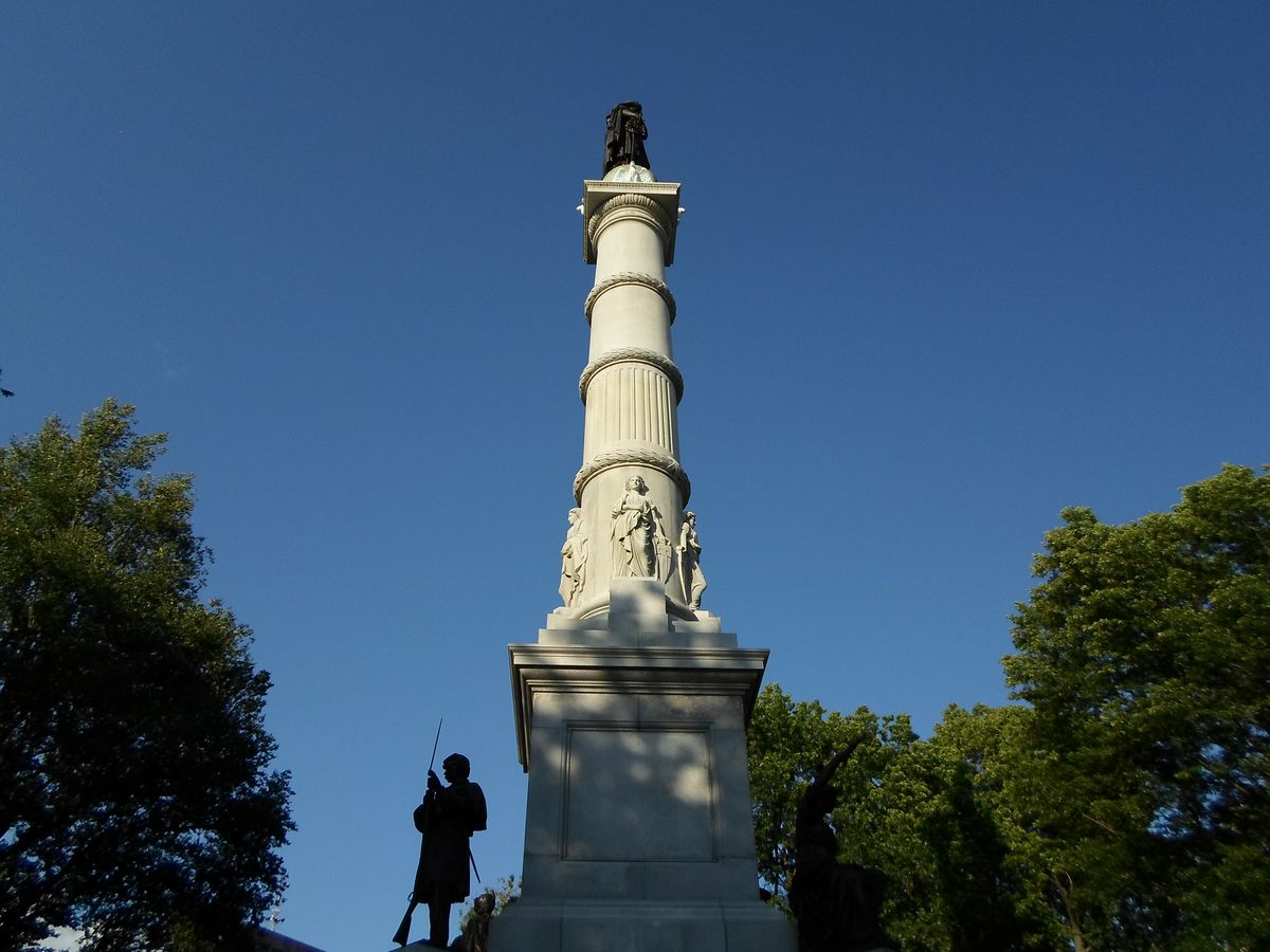 A tall, cylindrical monument with a bronze statue on top.