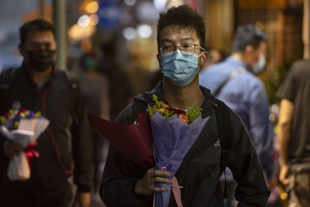 A man walking down the street with a surgical mask over his face carrying flowers in Hong Kong