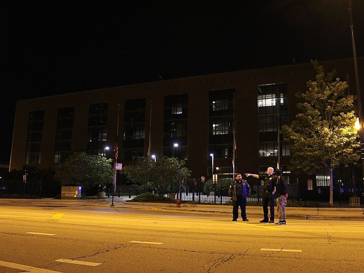 A witness to a shooting early Thursday recounts to officers what happened outside of the Domestic Violence Courthouse. | Daniel Brown/Sun-Times