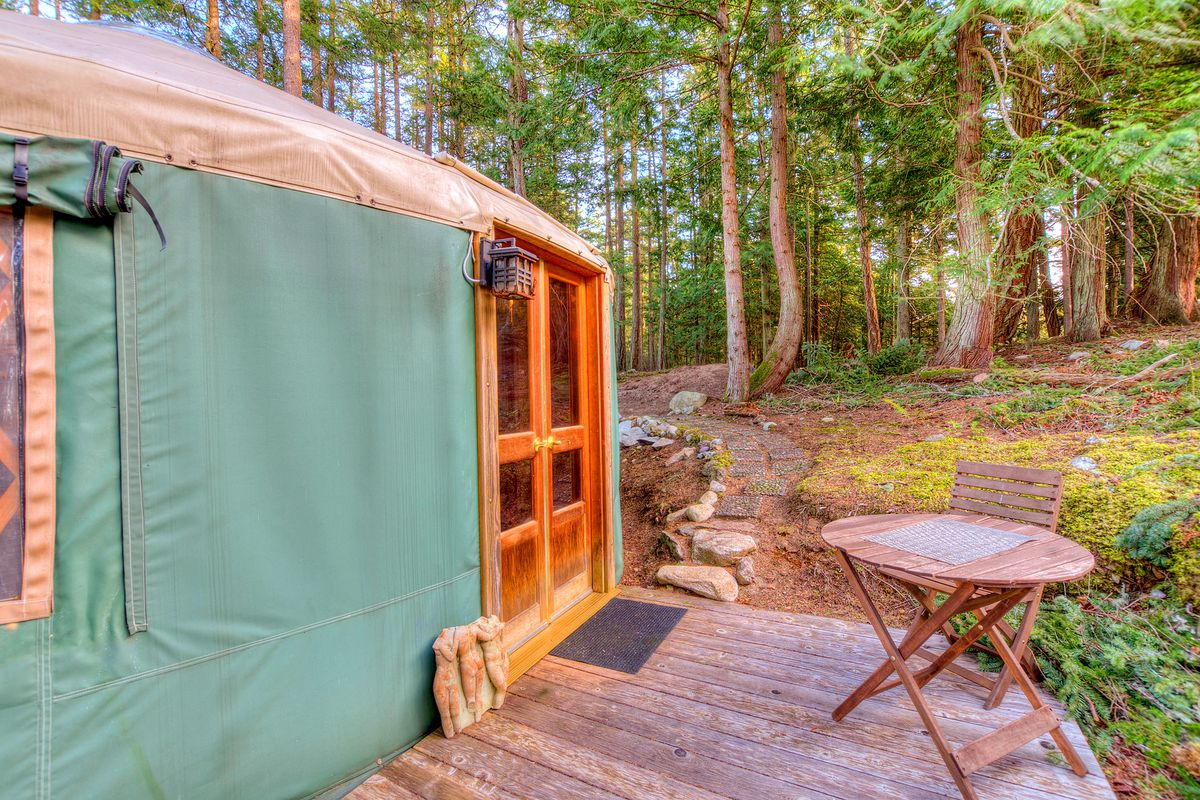The outside entrance to a green yurt with French doors