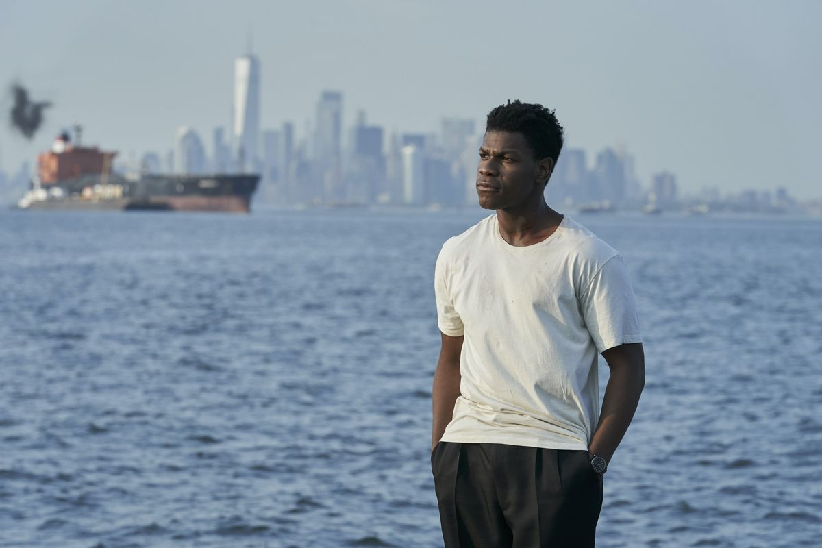 John Boyega, slouching in a white T-shirt and loose black pants, stands by water with Manhattan in the background in Naked Singularity