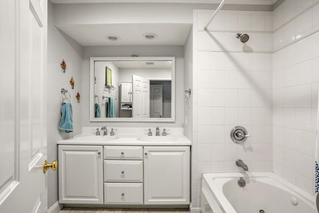 A bathroom facing the vanity with a mirror above it, and next to it is a tub with a the curtain pulled back.