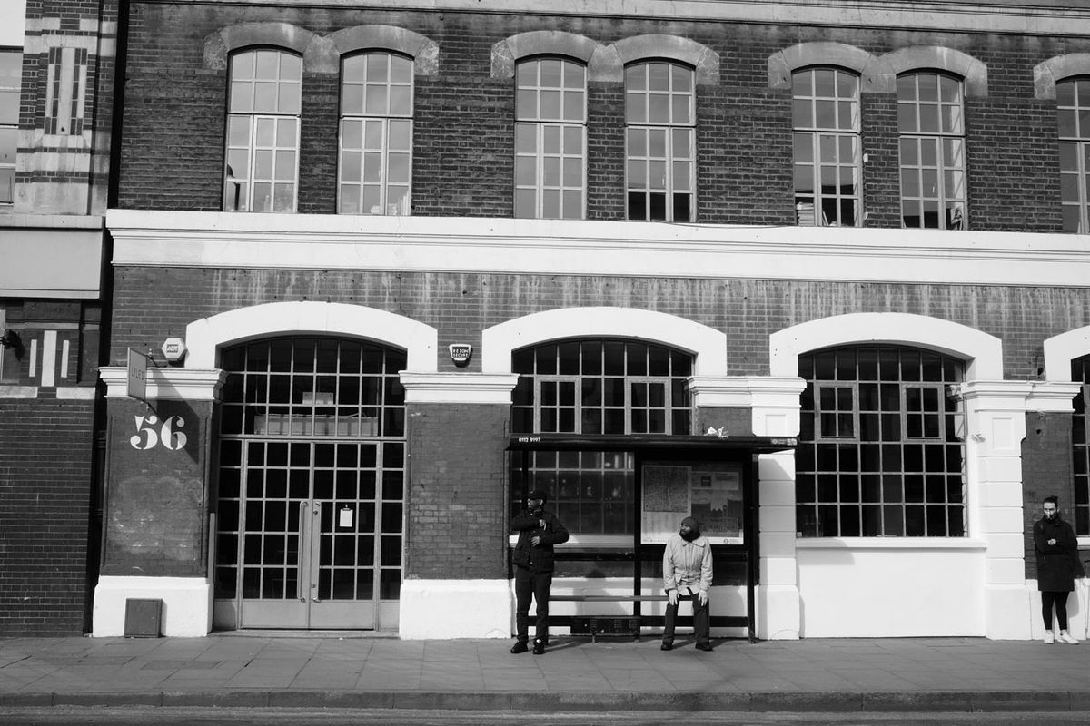 Londoners wait at a bus stop outside Lyle's restaurant in Shoreditch