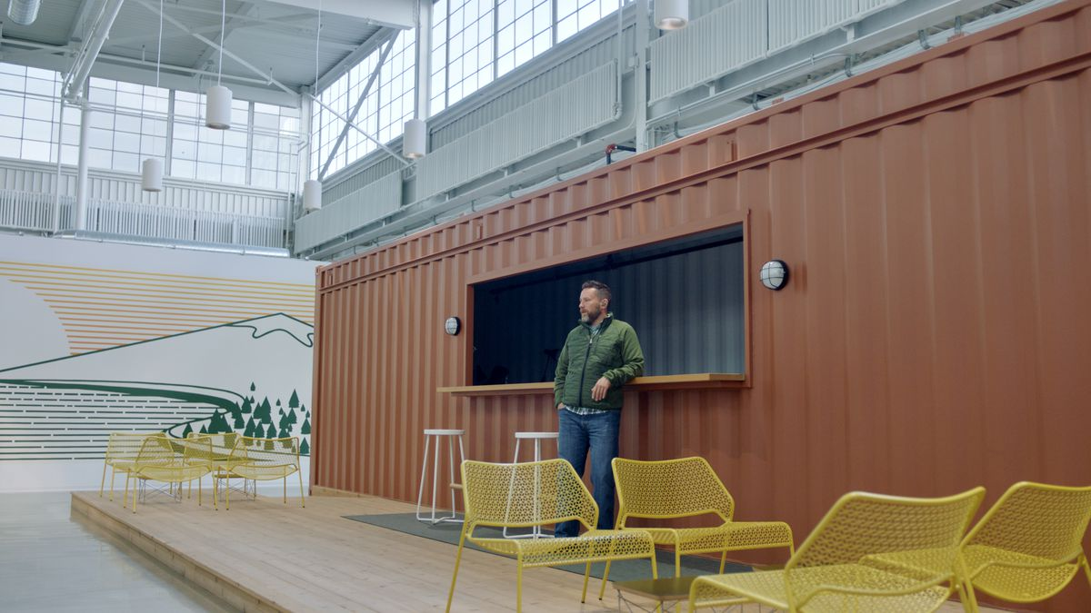 A man leans against an open space on a shipping container. Some yellow metal mesh chairs are nearby.