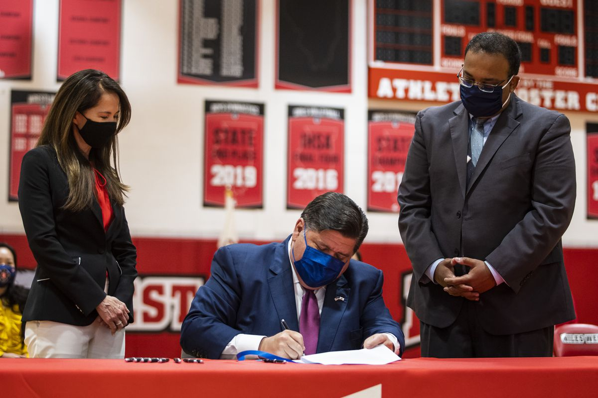 State Rep. Jennifer Gong-Gershowitz and state Sen. Ram Villivalam watch Gov. J.B. Pritzker sign legislation Friday that will require public school students to learn about Asian American history.