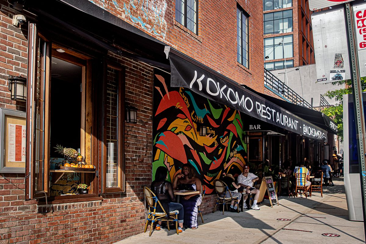 Customers sit on tables and chairs underneath a black awning next to a colorful mural painted on the side of a red brick building