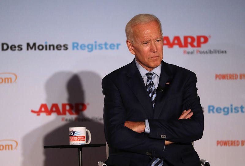 Former Vice President Joe Biden stands onstage with his arms crossed.