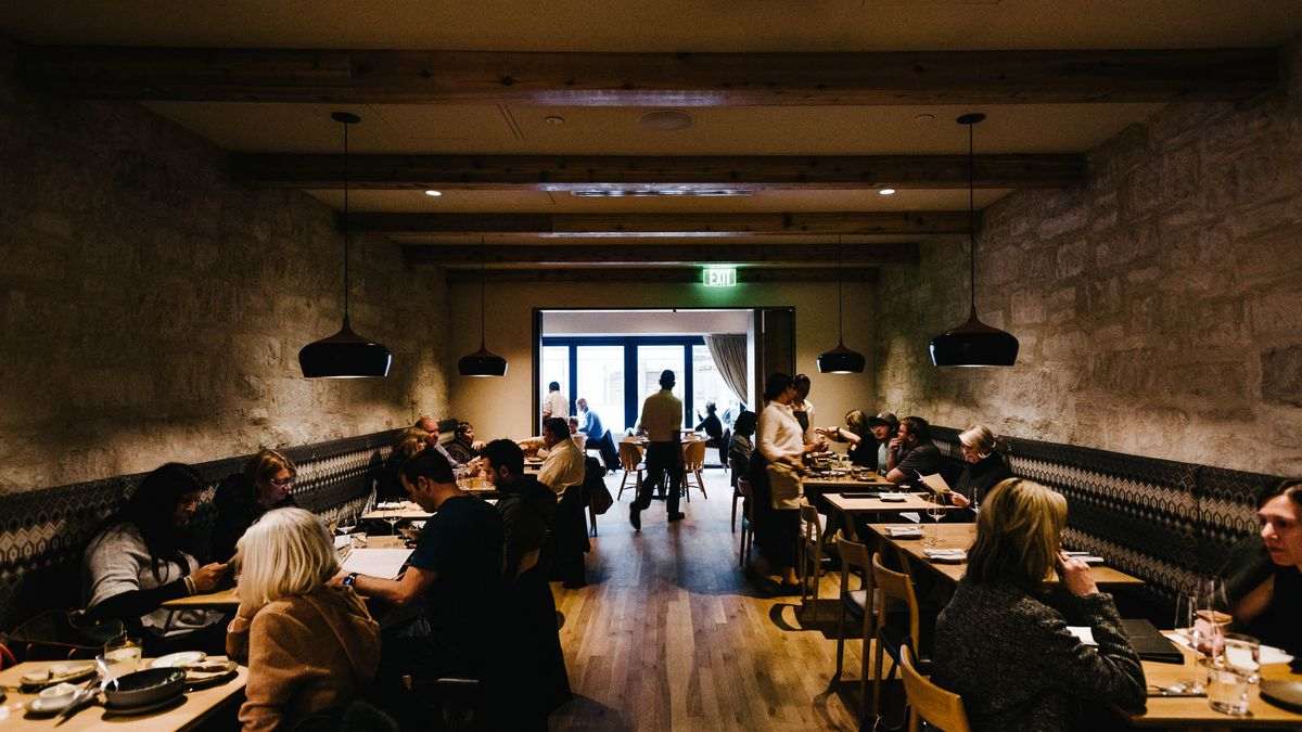 A view into the dining room at Tavernetta, where diners eat at tables while servers walk between them