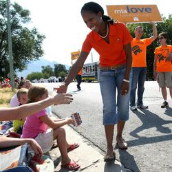 Mia Love greets people while walking in the Harvest Days Parade in Midvale on Saturday, Aug. 11, 2012. Behind her are her husband Jason Love and Becky Pirente, campaign political director.