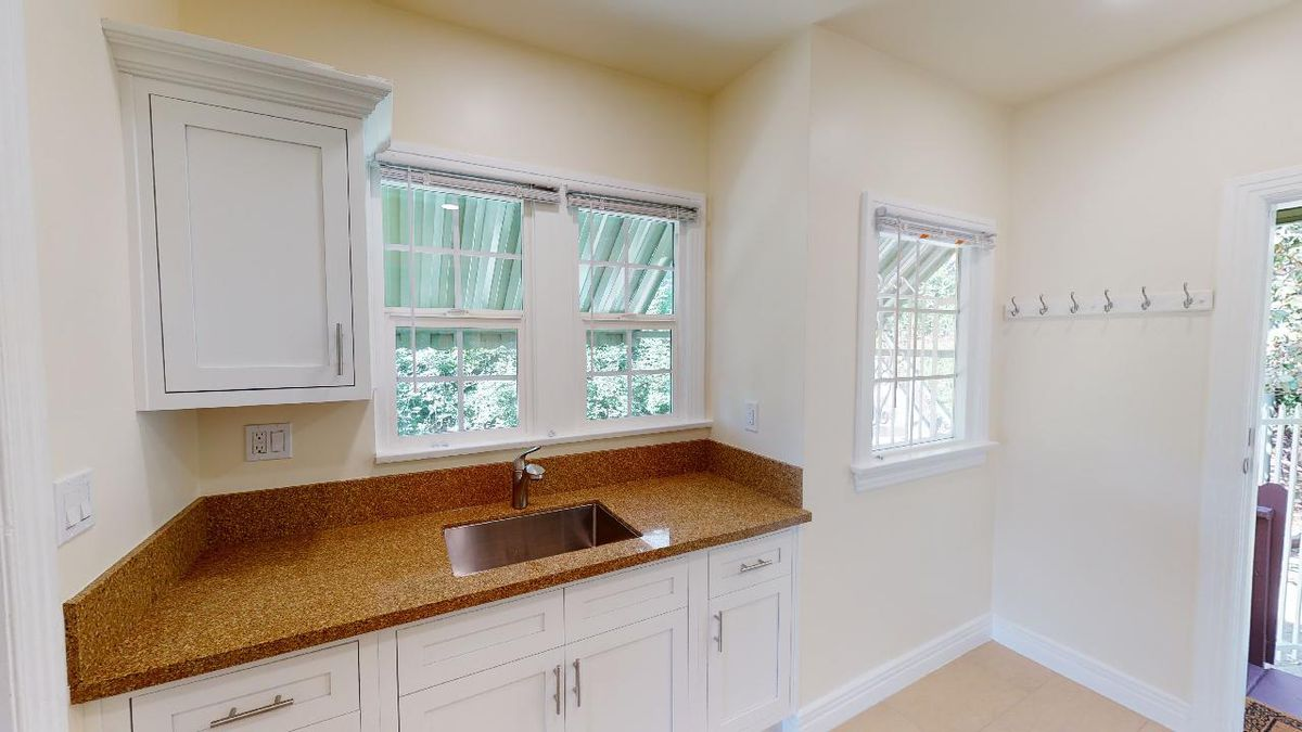 Kitchen with white cabinets and three windows.