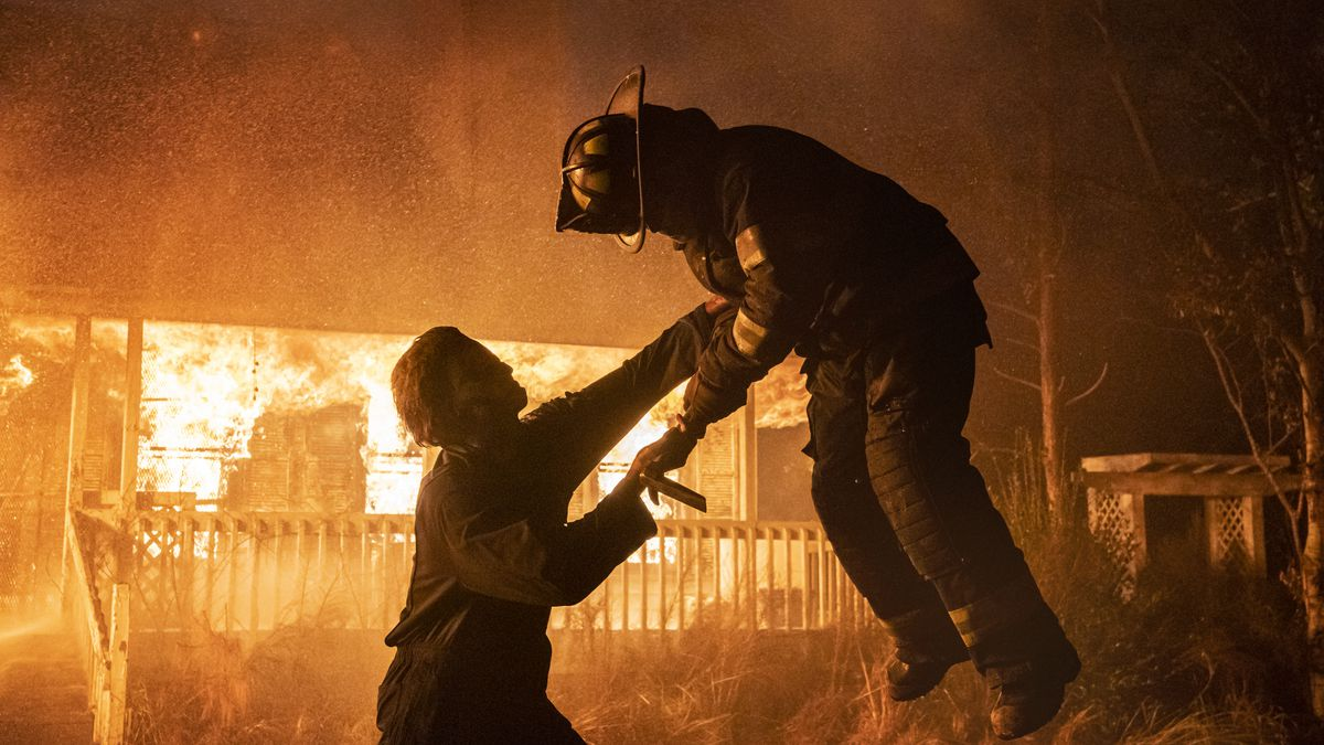 Michael Myers impales a firefighter in the air while a fire rages on behind them in Halloween Kills