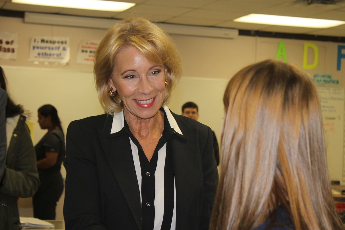 Betsy DeVos talks with a student in a health sciences program at Oakland High School in Murfreesboro, Tennessee.