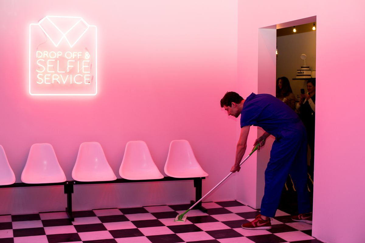 """Dream Machine """"drop off and selfie service"""" laundromat, man wiping checkered floor in a pink room"""