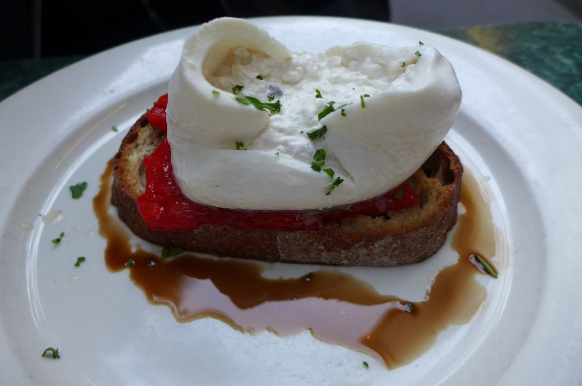 A mass of white burrata open at the top, and underneath red pepper, toast, and lake of brown balsamic.
