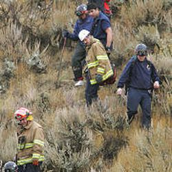 Salt Lake County rescue officials help the plane's woman passenger, upper center, walk down the steep slope to a waiting ambulance.