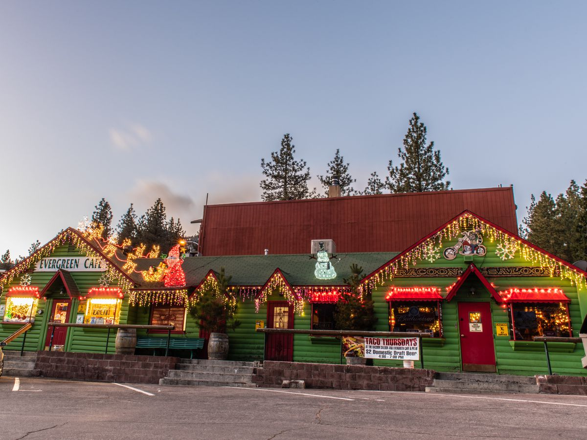 A long green building labeled Evergreen Cafe, decorated with strings of lights
