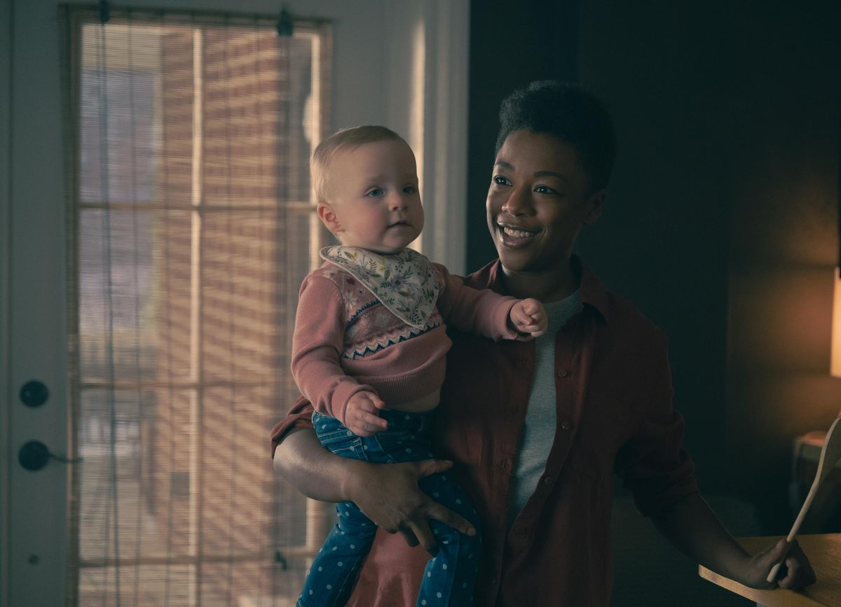 Moira holds baby Nichole in a sunlit room.