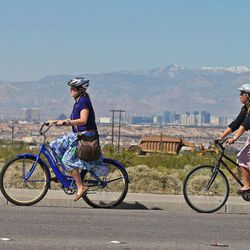 Sister Whitney Stoker, left, from Kennewick, Wash., and Sister Lauren Yoshimoto, from San Jose, Calif., bike along the streets of Henderson with the Las Vegas Strip in the background while visiting contacts in the Nevada Las Vegas Mission Friday, March 14, 2014, in Henderson.