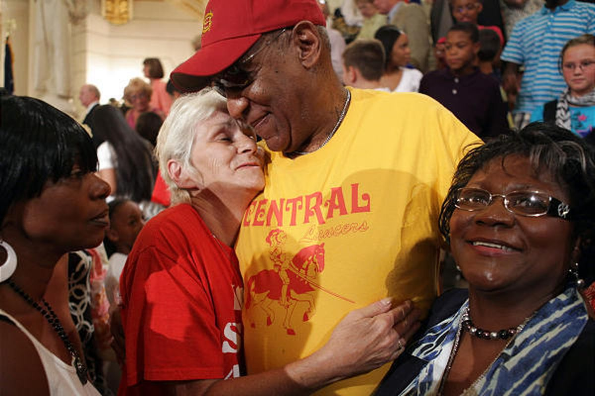 Comedian Bill Cosby, center, gets a squeeze from Linda Price, of Chambersburg, Pa., second from left, in the Capitol Rotunda in Harrisburg, Pa., Wednesday. Cosby joined Pennsylvania Gov. Ed Rendell at a news conference that celebrated steady improvements