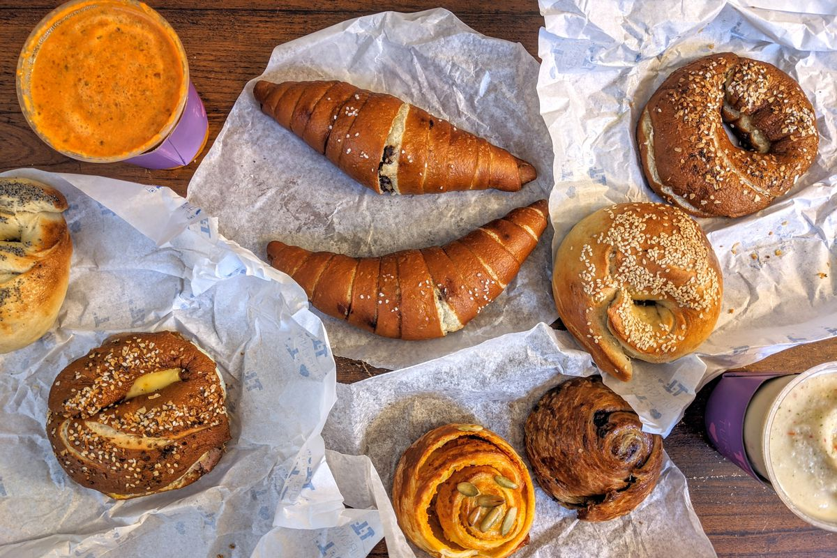 Overhead view of food spread out on white paper over a wooden tabletop: bagels, croissants, smoothies, and more.