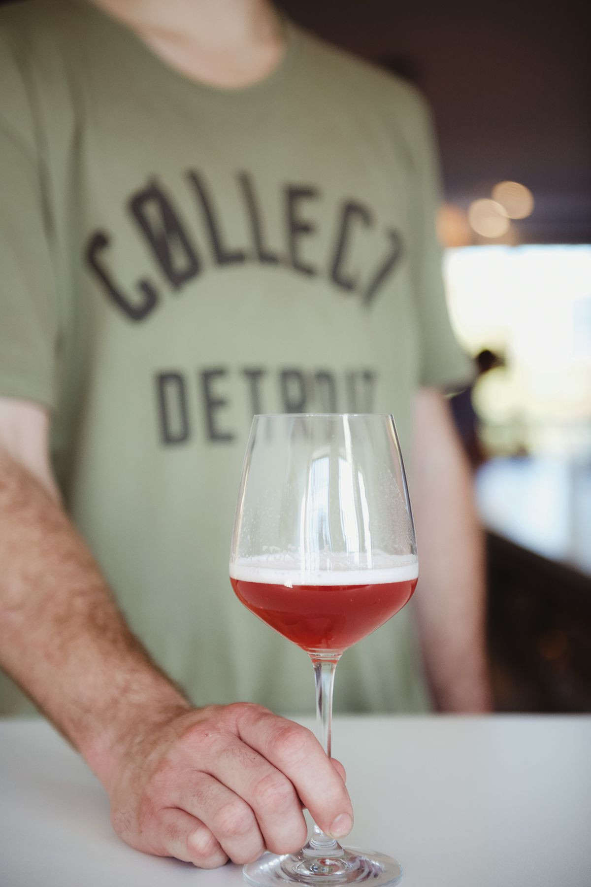 A man's white hand pushes a stemmed glass filled with a red beer toward the camera.