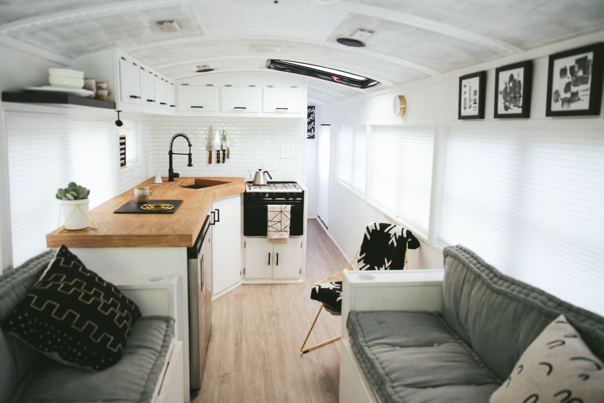 The interior of a camper van. The walls and ceiling are white. There are cushioned couches. There is a kitchenette with a sink and stove. There is art hanging on the walls.