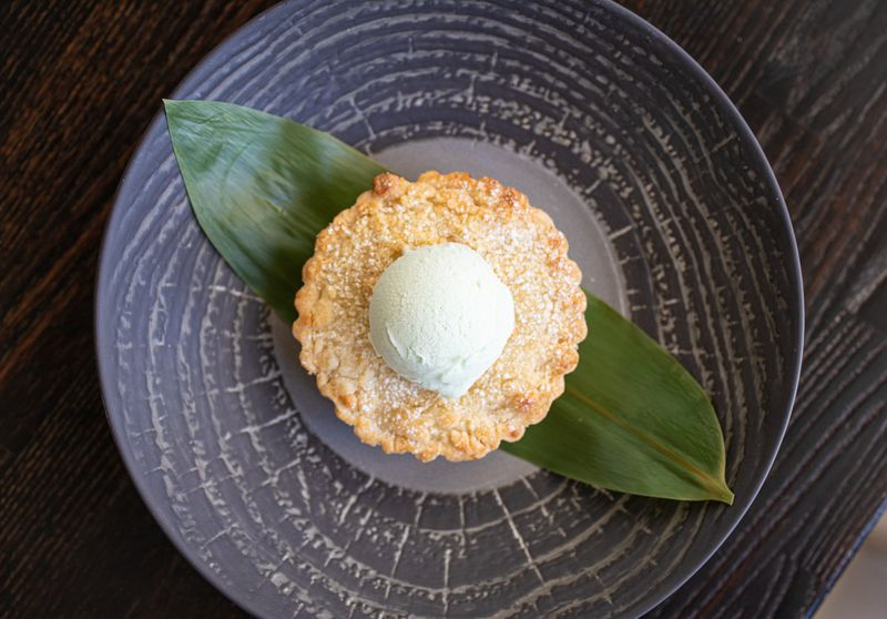 Young coconut tart with coconut pandan ice cream on a dark textured plate.