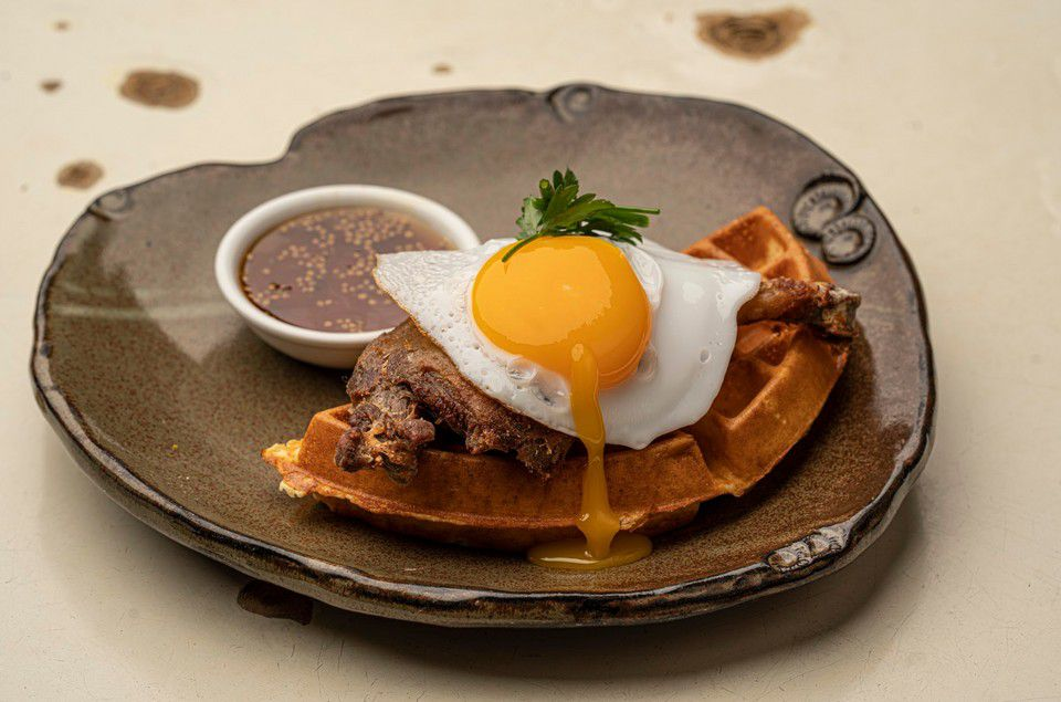 A waffle with duck and an sunny-side up egg