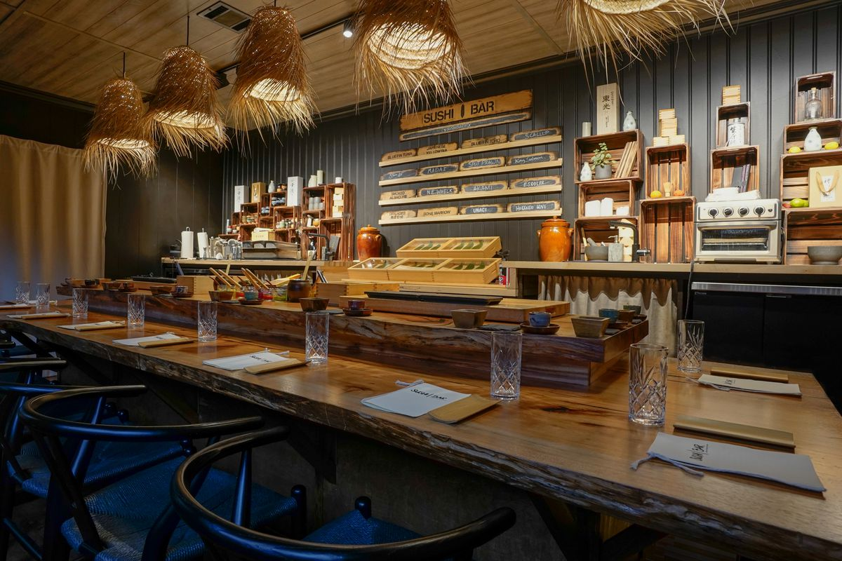 """A restaurant counter with menus and glasses in front of a bar with a sign that reads """"Sushi Bar"""" and hanging lights with hay"""