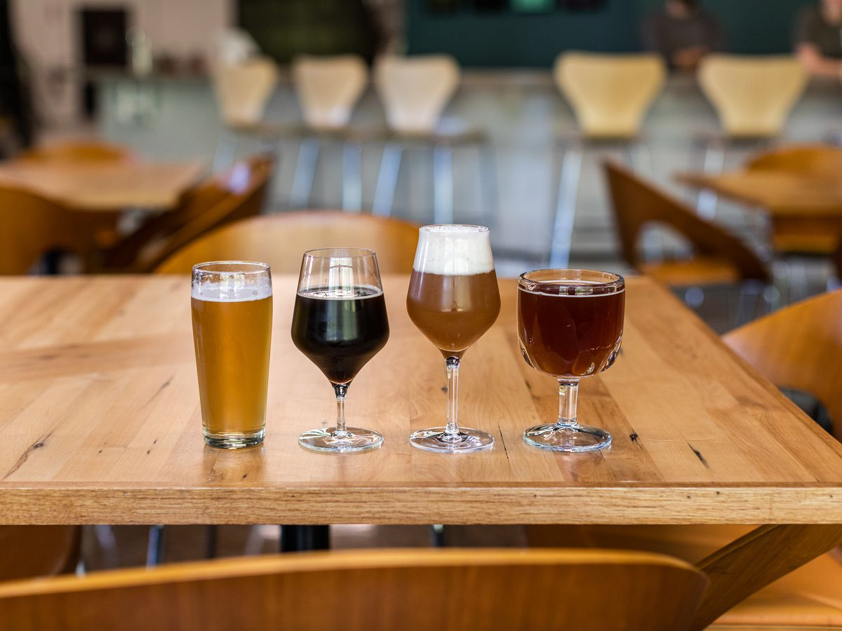 Four glasses of different colored beer in a row on a wooden table.