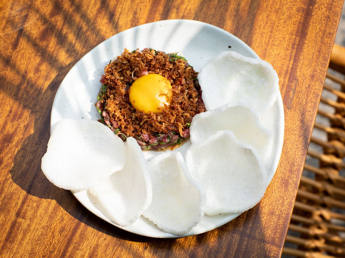 A red circle of steak tartare with a yellow egg yolk dropped in the middle, surrounded by white crab crackers set on a white plate with a wooden table in the background.